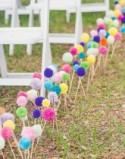 Use colorful yarn pom-poms as aisle decor