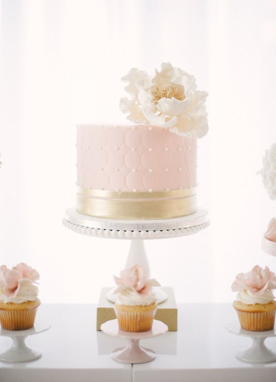 White and pink wedding cake with cupcakes
