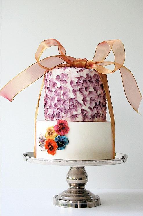 Hochzeit - Stiefmütterchen, Lila Blütenblättern und einem Shimmery Bogen füllen Sie dieses Zwei-Tier-Hochzeitstorte.