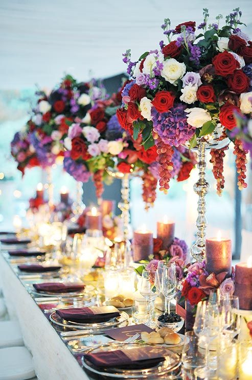 Opulent Centerpieces Of Red White And Purple Roses Hydrangeas Dangling Grapes Make A Bold Statement
