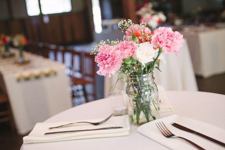 Pink and white carnations in mason jars for wedding