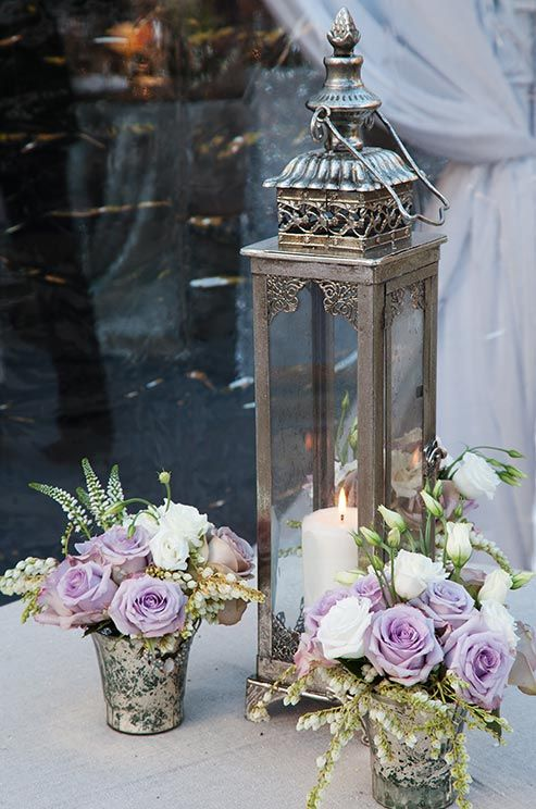 An Ornate Silver Lantern Was Arranged With Mercury Vases Of Lavender
