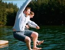 wedding photo - A canoe entrance, a dock jump, and a breastfeeding mama round out this fab camp wedding