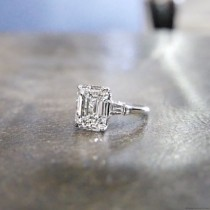 wedding photo - HALLE Is A Custom, Three Stones Engagement Ring Set In Platinum With An Emerald Cut Diamond And Two Tapered Baguettes, From Jewelry D…
