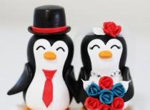 wedding photo - A penguin couple wedding cake topper. with red and green roses